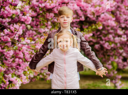Couple adorable lovely kids walk sakura garden. Tender love feelings. Little girl and boy. Romantic date in park. Spring time to fall in love. Kids in love pink cherry blossom. Love is in the air. - Stock Photo