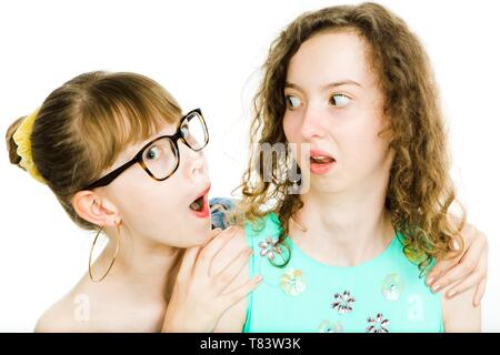 Two teenaged sisters posing together - looking at each other in funny way, jealousy friend - white background - Stock Photo