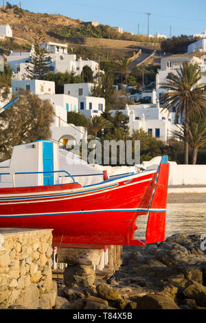 Mykonos Town, Mykonos, South Aegean, Greece. Colourful fishing boat on terrace of a waterfront taverna. - Stock Photo