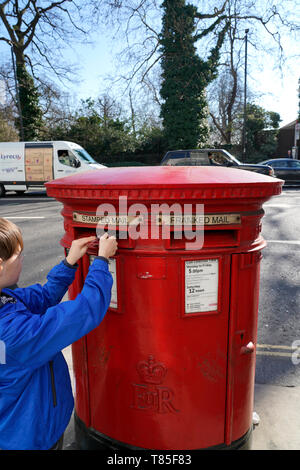 A boy posting a postcard in a red postbox in London, UK - Stock Photo