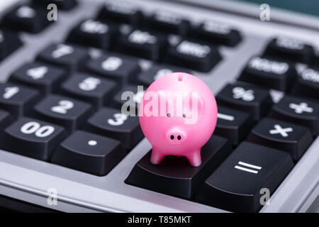 Close-up Of Small Pink Piggy Bank On Calculator - Stock Photo