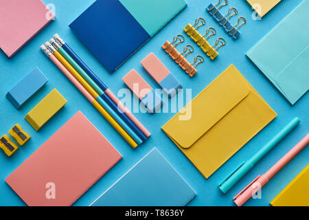 top view of notebooks and arranged colorful stationery isolated on blue - Stock Photo