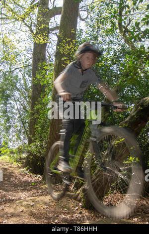 Boy doing jump on mountain bike - Stock Photo