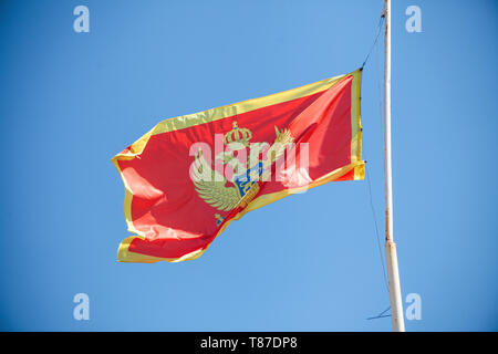 National flag of Montenegro against the blue sky. - Stock Photo