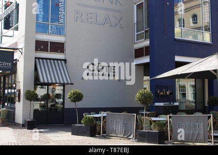 10 May 2019: Cardiff Bay, Cardiff UK:  Eateries in Cardiff Bay in the sunlight, waiting for the lunch hour rush. Cote Brasserie and Wagamama. - Stock Photo