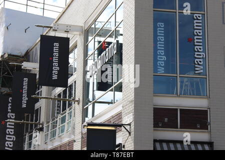 10 May 2019: Cardiff Bay, Cardiff UK:  Wagamama in Cardiff Bay, with scaffolding from construction work behind. - Stock Photo