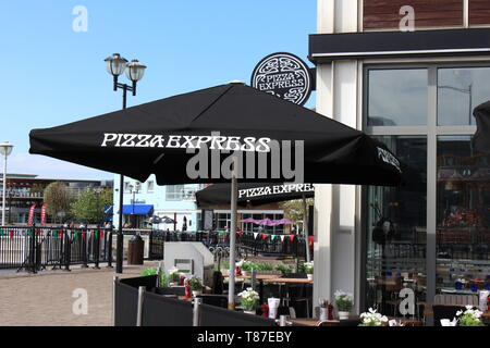 10 May 2019: Cardiff Bay, Cardiff UK:  Pizza Express in Cardiff Bay in the sunlight, waiting for the lunch hour rush.  Al fresco dining springtime. - Stock Photo