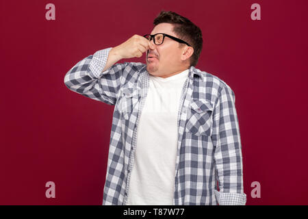 Portrait of bored handsome middle aged business man in casual checkered shirt and eyeglasses standing and blocking his nose because bad smell. indoor  - Stock Photo