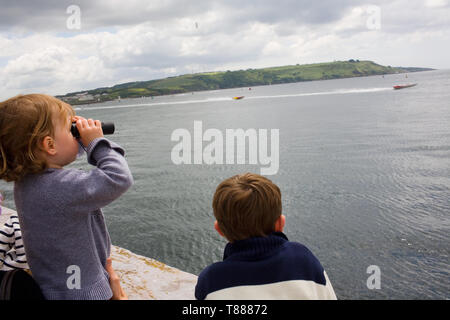 Fans watch the powerboats race across the water. - Stock Photo