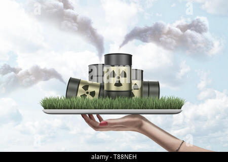 Woman's hand holding ipad with green grass growing on screen and pile of radioactive waste barrels on it puffing clouds of smoke all around. - Stock Photo