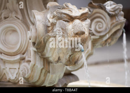 Closeup of the old royal fountain with lion spouting water in the heritage 'Fabrica Real de Tabacos' - ancient Royal Tobacco Factory in Seville, now - Stock Photo