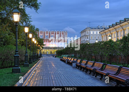 = Illuminated Alley in Morning Twilight =  Illuminated by old-style streetlights, the beautiful alley in Alexander Garden with wooden benches on the w - Stock Photo
