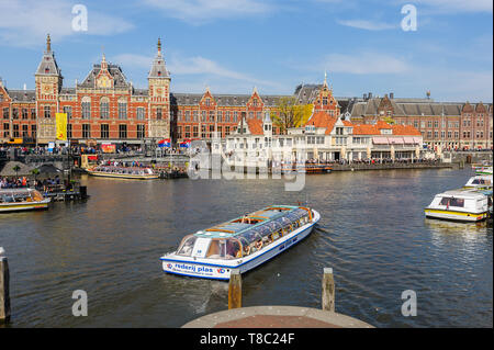Amsterdam, Netherlands - April 18, 2019: Tourists sightseeng at Canal Boats next to the Central Station of Amsterdam. - Stock Photo