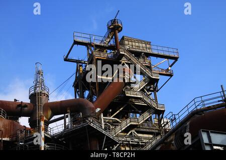Landschaftspark Duisburg, Germany: Low angle view on stairways into deep blue sky at corroded tower with rusty pipeline - Stock Photo