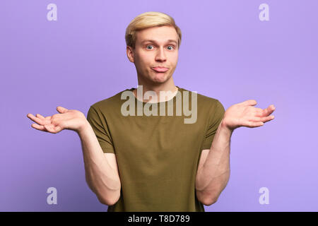 Clueless and puzzled young handsome man having confused expression, shrugging shoulders as if saying: I don't know - Stock Photo