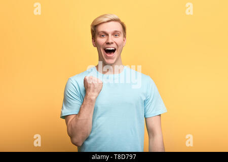 positive gorgeous young emotional man raising clenched fists in hooray gesture, rejoicing at his success. lick, happiness concepts , winner celebrating his victory - Stock Photo