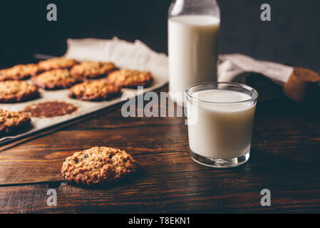 Homemade Oatmeal Cookies with Raisins and Glass of Milk for Breakfast. Some Cookies on Parchment Paper with Bottle on Backdrop. - Stock Photo