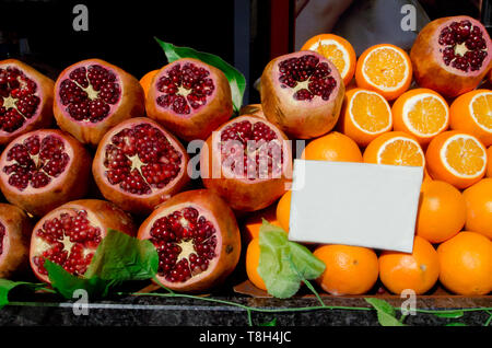 pile of raw oranges and pomegranates on street market, preparation of fresh juicy outdoor on sunny day, close up full frame - Stock Photo