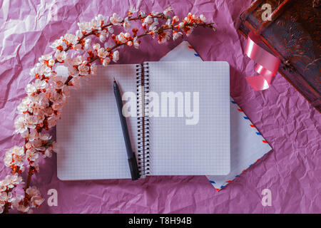 Opened notebook, pen and envelope in a frame of cherry blossoms on a bright background. Romance, love letters concept - Stock Photo