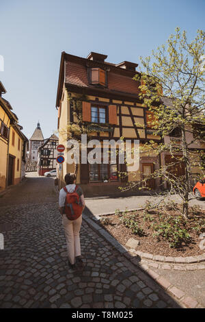 Female tourist sightseeing the traditional village of Bergheim in Alsace France discovering the old half-timbered buildings and the tiny cobblestone pavement streets  - Stock Photo
