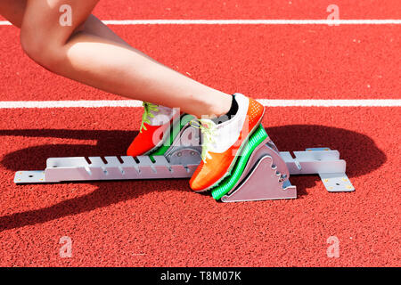 A female high school sprinter is in the 'set' position in the starting blocks on a red track at track and field practice outside on a sunny day. - Stock Photo