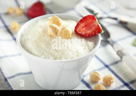 Delicious rice pudding with strawberry and hazelnuts in bowl on table - Stock Photo