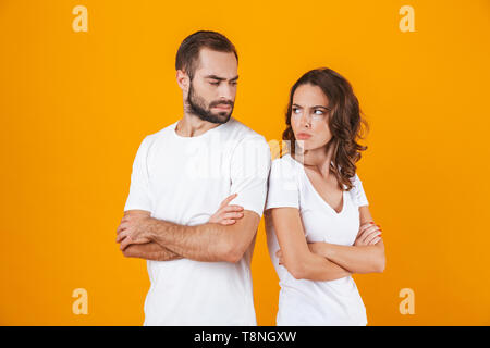 Photo of unhappy man and woman in quarrel standing back to back with arms folded isolated over yellow background - Stock Photo