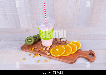 Fresh smoothie on wodeen table, assorted protein cocktails with nuts and fresh fruits - Stock Photo