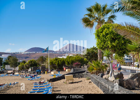 LANZAROTE, CANARY ISLANDS, SPAIN - APRIL 15, 2019: People relax on the beach. View of volcanic hills, ocean and blue sky/sun loungers on the beach - Stock Photo