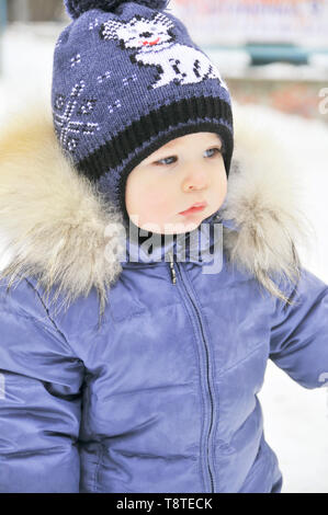 Baby in winter overalls wrapped in a scarf walks on a snow-covered street and sculpts from snow. - Stock Photo