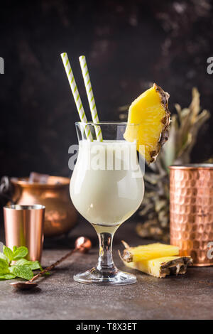 Homemade frozen Pina Colada cocktail with rum, coconut milk and pineapple garnish over black background - Stock Photo
