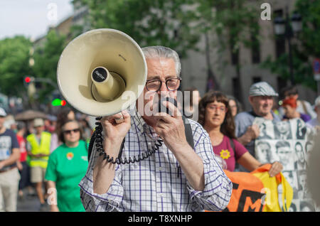 Madrid, Spain. 15th May, 2019. A march celebrating the 8th anniversary of 15M took place through the main streets of the city center. In the picture the spokesman of the protest is walking with the demonstrators behind. Credit: Lora Grigorova/Alamy Live News - Stock Photo