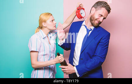 After corporate party. Man suffering from alcoholism. Angry wife meeting drunk husband late at home. Businessman with alcohol bottle and woman with alarm clock. Addictive alcoholism or alcohol abuse. - Stock Photo