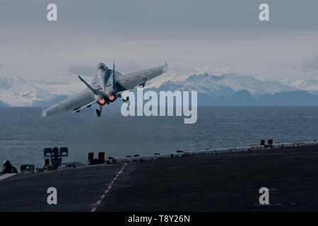 A U.S. Navy F/A-18F Super Hornet fighter aircraft, assigned to the Black Knights of Strike Fighter Squadron 154, launches from the flight deck of the aircraft carrier USS Theodore Roosevelt during Exercise Northern Edge 2019 May 13, 2019 in the Gulf of Alaska. - Stock Photo