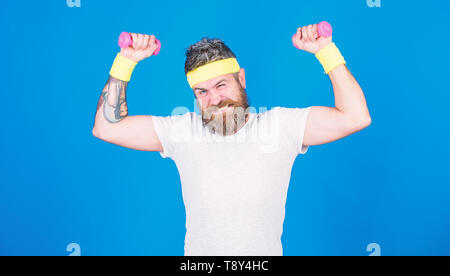 Improve your muscles. Use weights or dumbbells. Man bearded athlete exercising dumbbell. Athlete training with tiny dumbbell. Motivated athlete guy. Sportsman training with dumbbells blue background. - Stock Photo