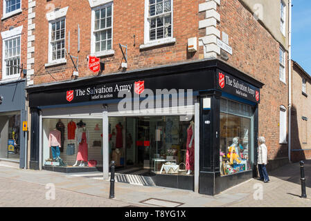 Woman looking in window of the Salvation Army charity shop on a high street corner in the Worcestershire market town of Evesham - Stock Photo