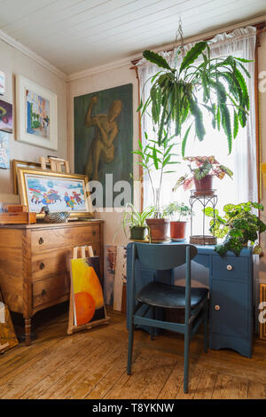 Paintings, hanging and potted green plants ontop of blue desk in upstairs room inside an old 1927 American Four Squares house, Quebec, Canada. This image is property released. CUPR0221 - Stock Photo