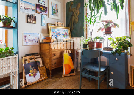 Paintings, hanging and potted green plants on wooden shelves and in white wicker basket table and on top of blue desk in upstairs room inside an old 1927 American Four Squares house, Quebec, Canada. This image is property released. CUPR0221 - Stock Photo