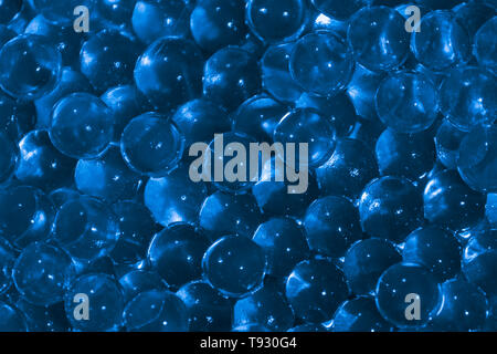 Transparent blue hydrogel balls. Blue water gel balls with bokeh. Polymer gel Silica gel. Liquid crystal ball with reflection. Blue balls texture back - Stock Photo