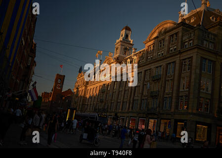 Crowds of people walking along the street passed the famous Bijenkorf department store in the city centre of Amsterdam in spring sunshine - Stock Photo