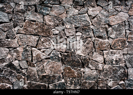 textured texture of a dark and gray old stone wall. Wallpaper for background and design - Stock Photo