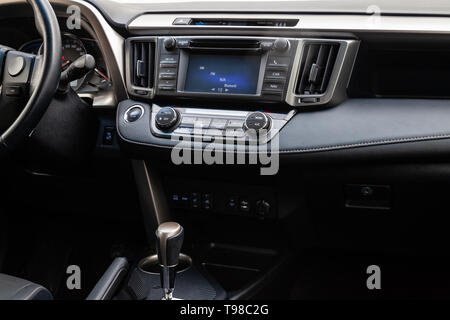 Comfortable front seats inside the car: the driver and passenger, tied with genuine black leather, modern interior design, the steering wheel covered  - Stock Photo