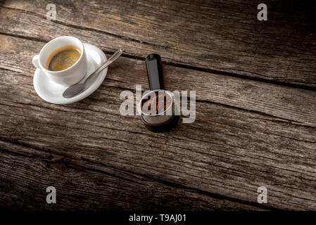 Cup of fresh hot Arabica black coffee and freshly ground coffee beans in the metal measure of a coffee machine lying on a textured rustic wooden board - Stock Photo