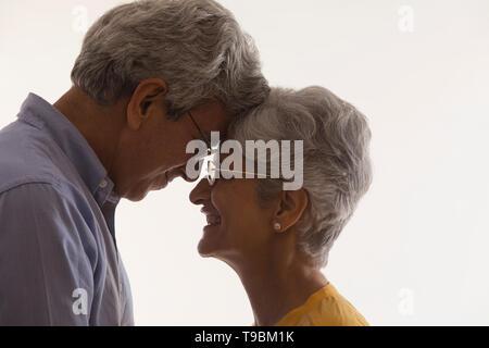Portrait of senior couple touching foreheads - Stock Photo