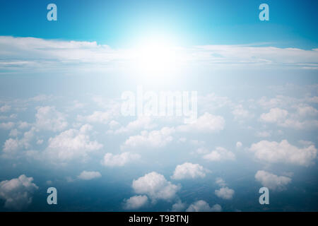 View of the sky clouds above the clouds from airplane window with sun light retro color filter - Stock Photo