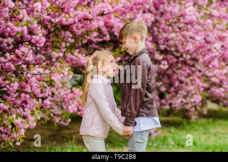 Love is in the air. Tender love feelings. Little girl and boy. Romantic date in park. Spring time to fall in love. Kids in love pink cherry blossom. Couple adorable lovely kids walk sakura garden. - Stock Photo