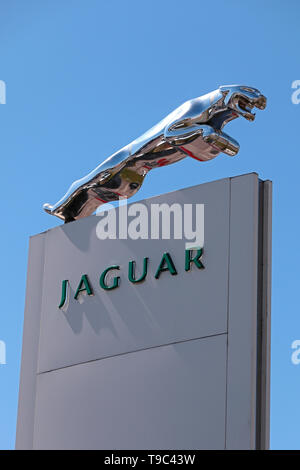 Jaguar Dealership sign with sculpted silver Jaguar Cat emblem - Stock Photo