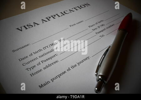 Visa application form with a pen for filling out. Document For applying to enter in a foreign country. - Stock Photo