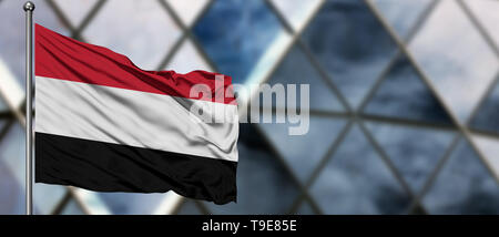 Yemen flag waving in the wind against blurred modern building. Business concept. National cooperation theme. - Stock Photo