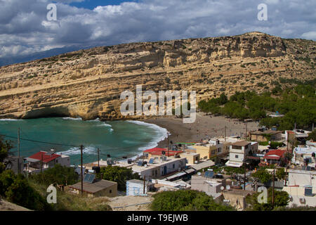 Matala, a village on Crete, early Christian tombs, carved out in the sandstone rocks behind the village - Stock Photo